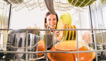 Young Happy Woman Arranging Plates In Dishwasher FOTO: Andreypopov Getty Images/istockphoto