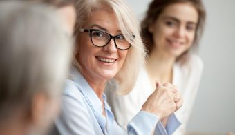 Smiling aged businesswoman in glasses looking at colleague at team meeting, happy attentive female team leader listening to new project idea, coach mentor teacher excited by interesting discussion FOTO: Fizkes Getty Images/istockphoto