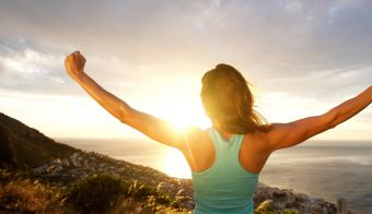 Portrait of woman from behind stretching out her arms in front of sunrise FOTO: M-imagephotography Getty Images/istockphoto
