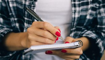 Woman in plaid shirt and a red manicure pen writing in a notebook FOTO: Iprogressman Getty Images/istockphoto