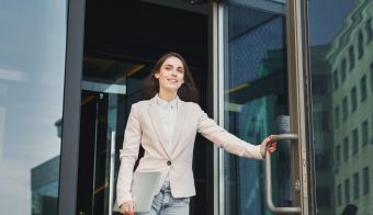 Happy confident businesswoman walking out of modern office center, holding laptop outdoors, copy space FOTO: Milkos Getty Images/istockphoto