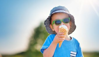 Happy child eating ice cream outdoors in summer. Portrait of a boy in sunglasses on sunny day FOTO: Lemanna Getty Images/istockphoto