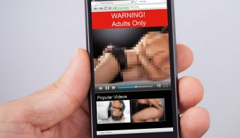 Close-up Of Person's Hand Holding Mobile Phone Showing Adult Movie FOTO: Andreypopov Getty Images/istockphoto