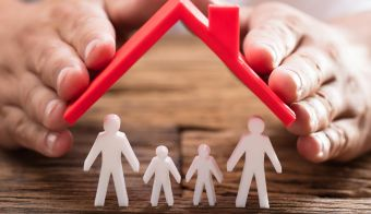 A person's hand protecting family figures with red roof on wooden desk FOTO: Andreypopov Getty Images/istockphoto
