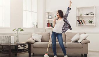 Happy woman cleaning home, singing at mop like at microphone and having fun, copy space. Housework, chores concept FOTO: Milkos Getty Images/istockphoto