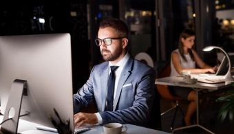Handsome young businessman in the office with his coworker at night working late. FOTO: Halfpoint Getty Images/istockphoto