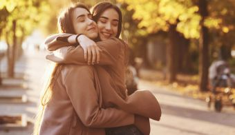 Side profile of young pretty smiling brunette twin girls hugging and having fun in casual coat standing close to each other at autumn sunny park alley on blurry background.