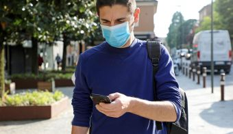 COVID-19 Pandemic Coronavirus Worried Young Man Wearing Surgical Mask Using Smart Phone App in City Street to Aid Contact Tracing and Self Diagnostic in Response to the Coronavirus Pandemic 2019. FOTO: Zigres / Shutterstock FOTO: Zigres Shutterstock